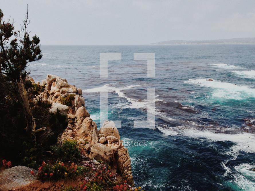 Ocean waves at a shoreline of rocks.