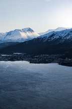 snow on mountains and homes along a shore