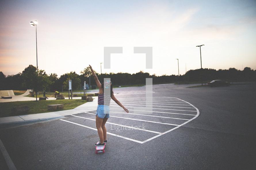 woman on a skateboard in a parking lot