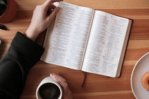a woman reading a Bible and coffee and donuts