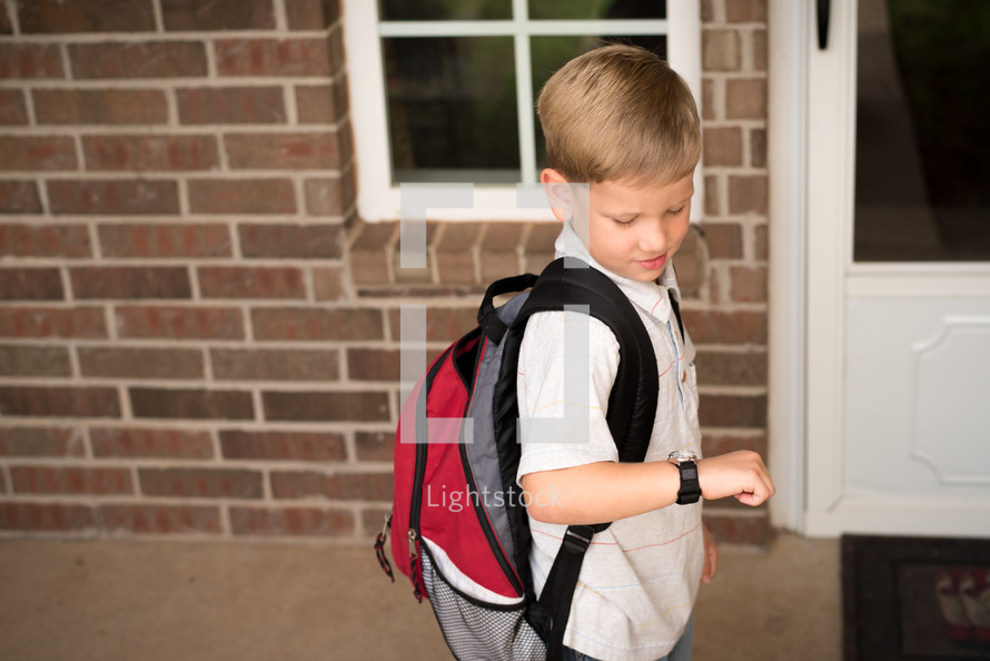 a little boy with a book bag looking at his watch