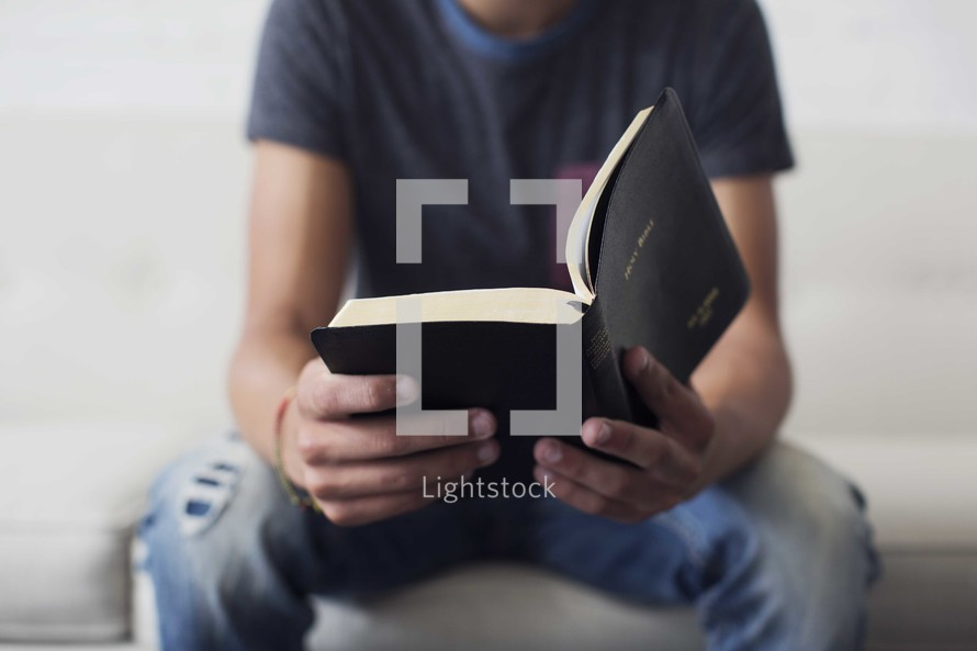 a teen boy reading a Bible on a couch.