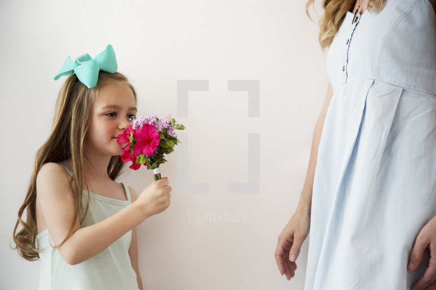 a little girl smelling flowers.