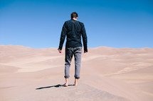man standing barefoot in the desert
