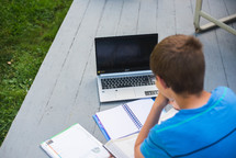 a child working on school work outdoors