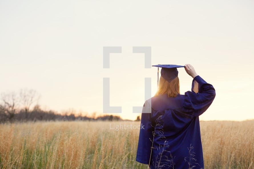 female graduate walking through a field of tall grasses