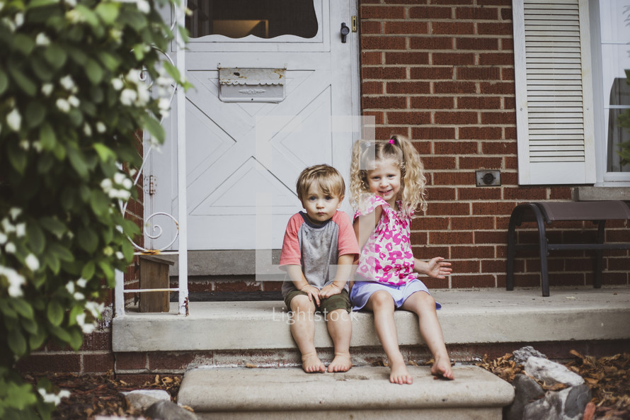 kids sitting on steps on a front porch
