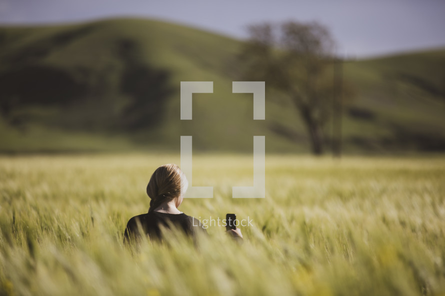 a woman holding a cellphone standing in a field of tall grasses