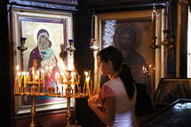 Lighting a votive or prayer candle before icons of Christ and Mary the mother of Christ