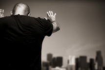 A man praying over a city - hands raised