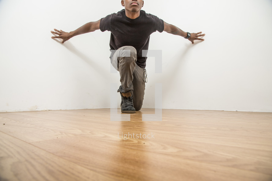man pushing against a wall