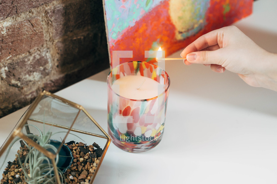 lighting a candle with a match