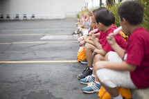 children eating popsicles sitting on the curb