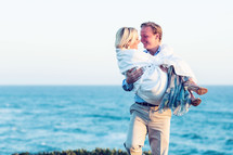 Husband carrying his wife on the beach at the ocean.