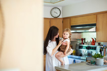 a mother holding her daughter in a kitchen