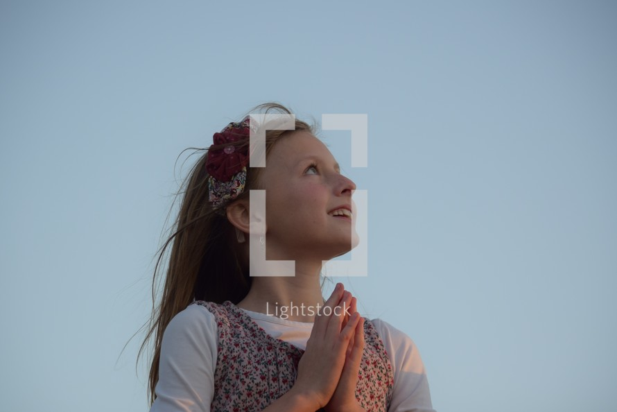 A little girl looking up to God with praying hands, child of god, hopeful