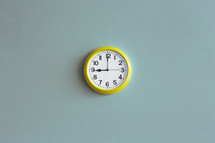 A yellow wall clock on a blue wall.