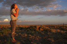 a girl praying outdoors at sunset