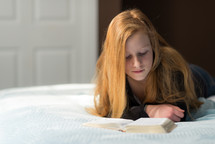 teen girl reading a Bible on a bed