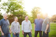 men standing in a backyard talking