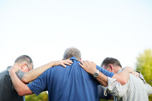 a group of men praying together outdoors