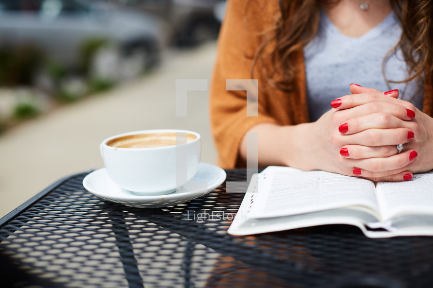a woman sitting at an outdoor table reading a Bible and praying