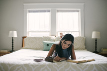 A teen girl taking notes and studying the Bible while laying on her bed.