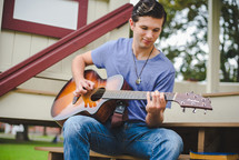 A young man plays a guitar outside.
