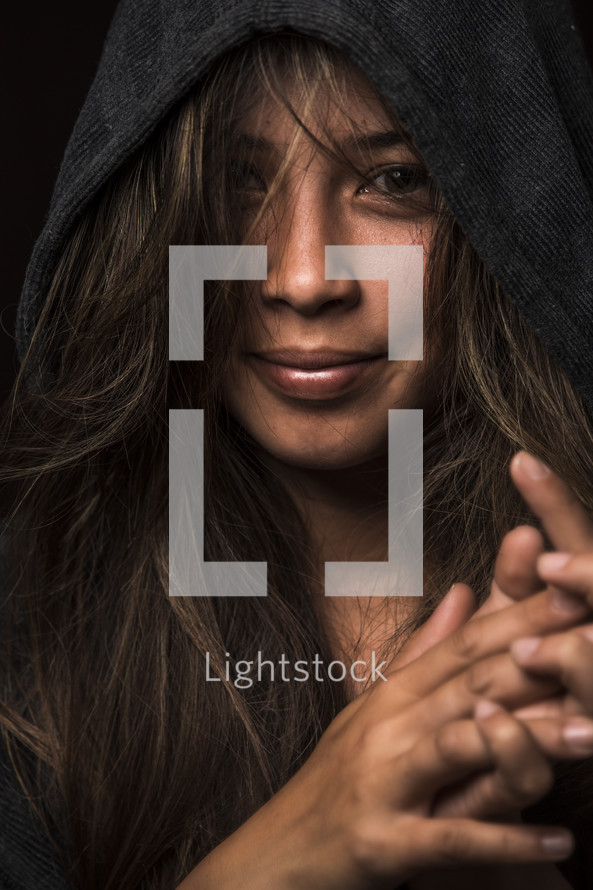 stoic face of a woman wearing a hoodie