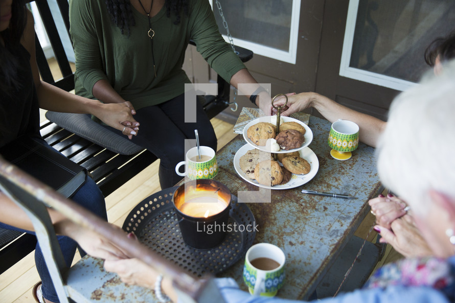 woman's group Bible study on a porch praying together