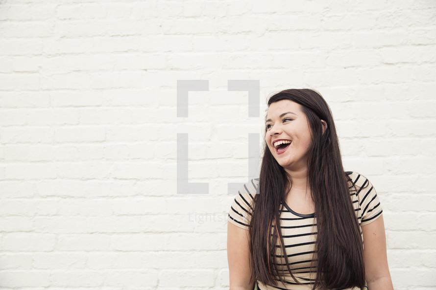 a joyful young woman laughing.