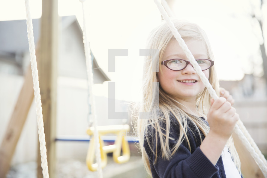 A little girl on a swing set.