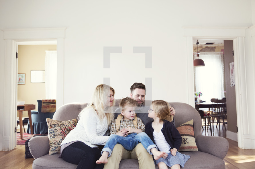 A family sits together on a couch in their living room.