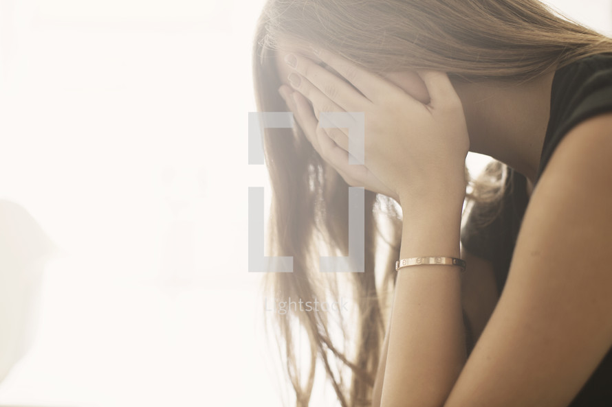 a teenage girl covering her face with her hands.