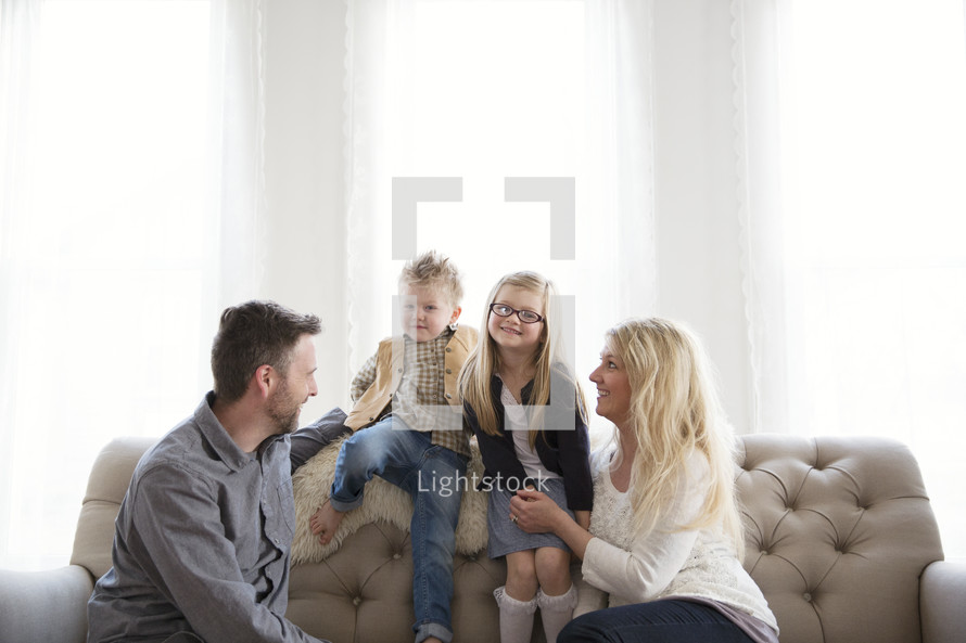 A family of four sits together on a couch.