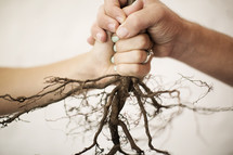 man and woman holding onto roots