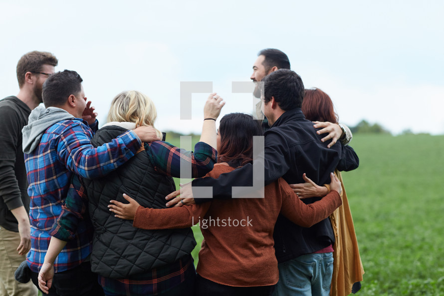a united group of people standing with arms around each other
