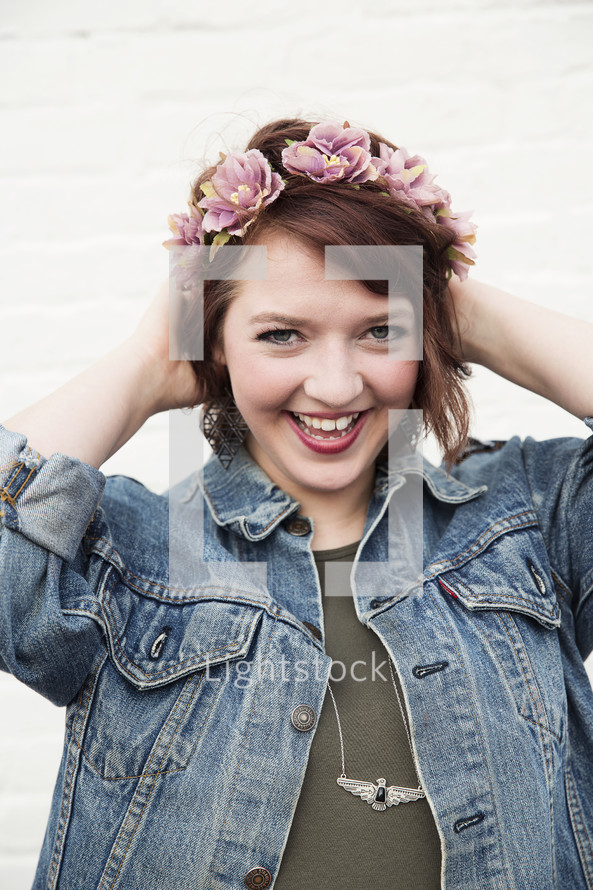 A smiling young woman with flowers in her hair.