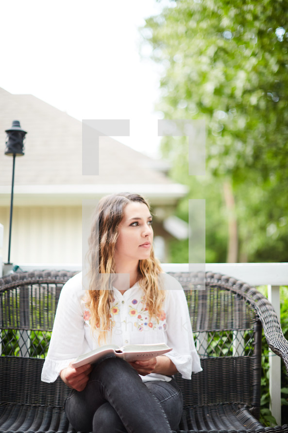 a young woman sitting on a porch reading a Bible