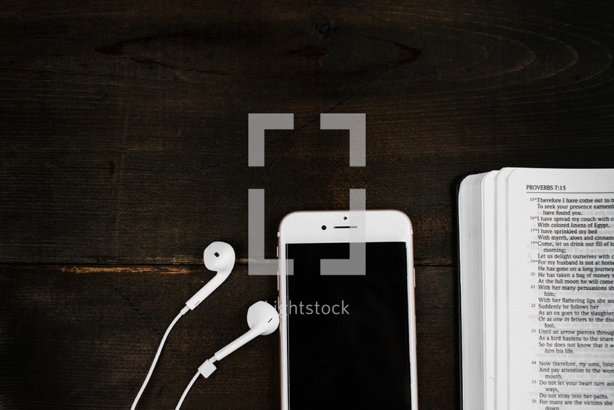 iPhone with earbuds and open Bible