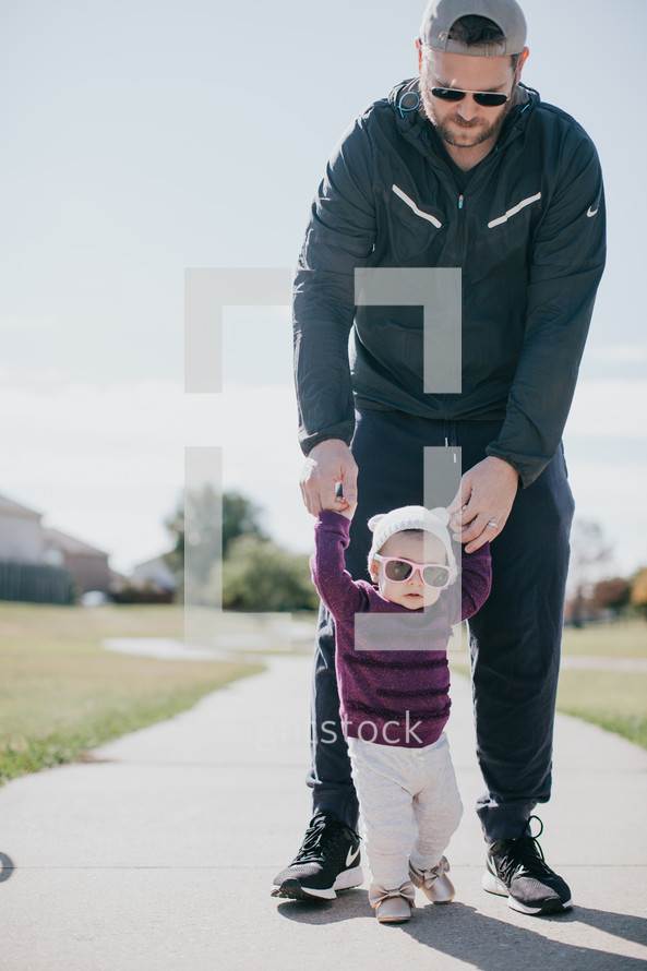 a father helping his infant daughter learn to walk