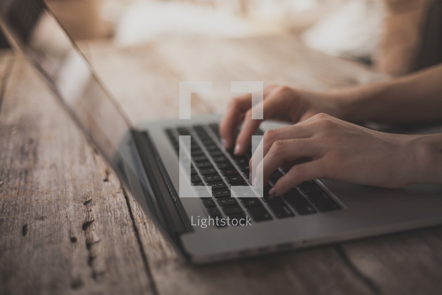 Hands typing on a laptop on a wooden table.