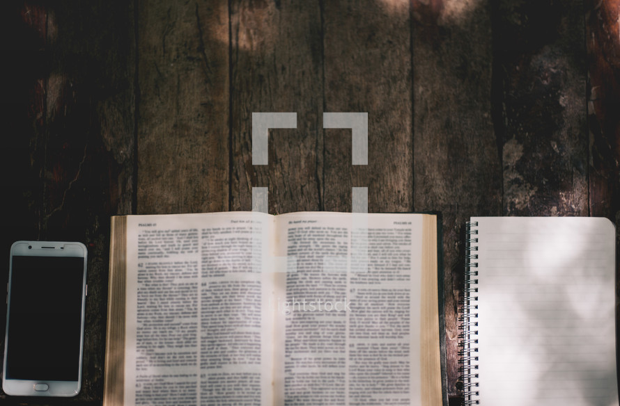 cellphone, open Bible, notebook, on a wood background