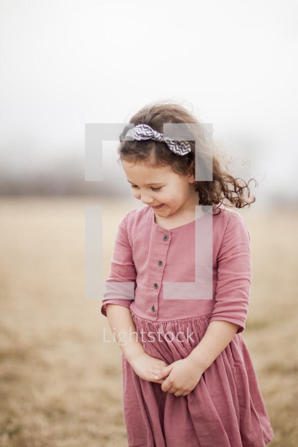 Little girl smiling in a foggy field