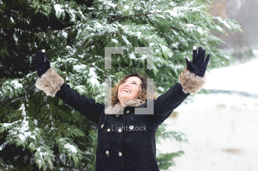 a woman standing in the snow with raised hands