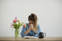 a woman sitting at a desk with a mug of coffee and a vase of tulips praying over a Bible