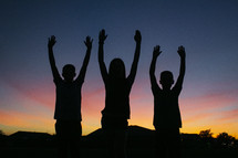 silhouettes of children with hands raised