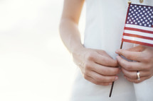 Hands holding an American flag.