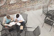 men reading Bibles at an outdoor cafe Bible study