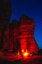 campfire beside red rocks cliffs at night
